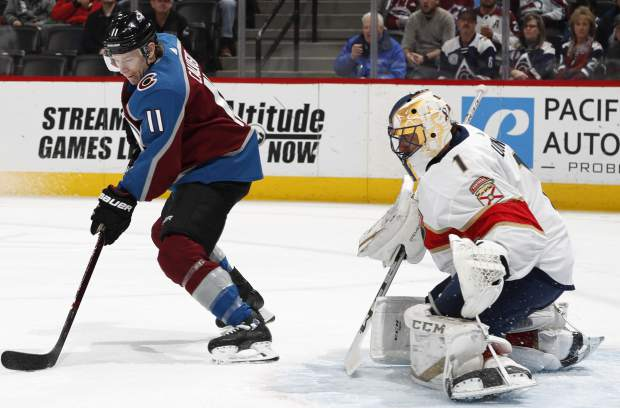 Colorado Avalanche left wing Matt Calvert, left, directs a shot at Florida Panthers goaltender Roberto Luongo in the first period of an NHL hockey game Monday, Feb. 25, 2019, in Denver. (AP Photo/David Zalubowski)