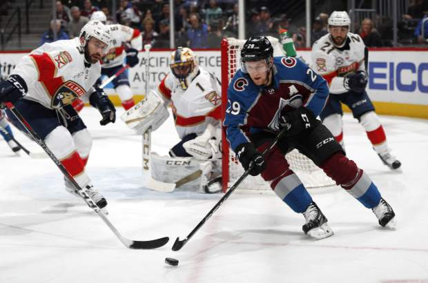 Colorado Avalanche center Nathan MacKinnon, front right, wraps around the net for a shot as Florida Panthers defenseman Keith Yandle, front left, and goaltender Roberto Luongo cover in the first period of an NHL hockey game Monday, Feb. 25, 2019, in Denver. (AP Photo/David Zalubowski)