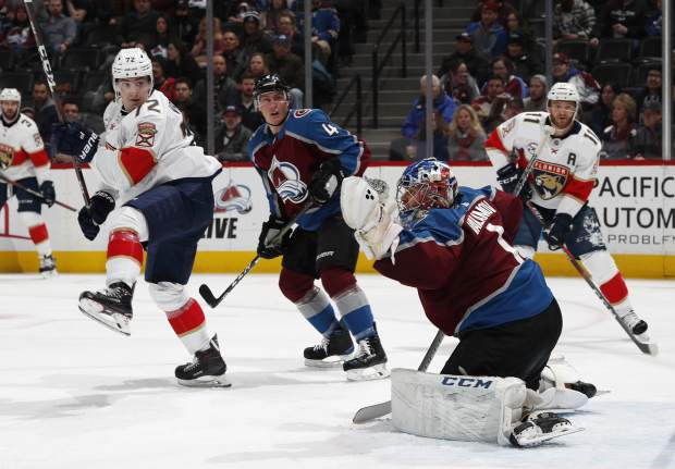 Florida Panthers center Frank Vatrano, left, looks on with Colorado Avalanche defenseman Tyson Barrie as goalie Semyon Varlaov makes a glove-save of a shot in the second period of an NHL hockey game Monday, Feb. 25, 2019, in Denver. (AP Photo/David Zalubowski)