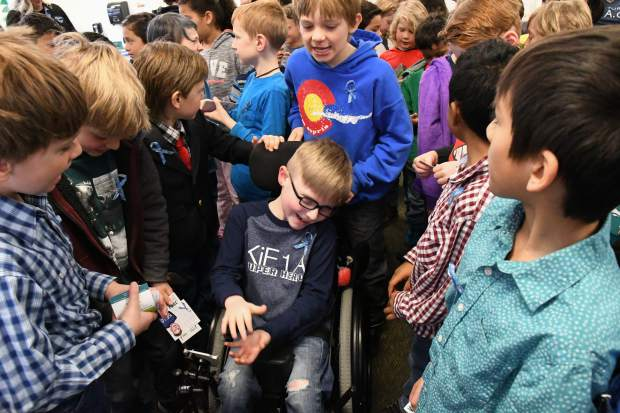 Sopris Elementary School third-grader Turner Fautsko is embraced by his friends and fellow classmates after a presentation about Rare Disease Day. Fautsko was diagnosed with a rare genetic condition, KiF1A Associated Neurological Disorder. His mother, Jenni, gave the presentation to the third graders at the school on Thursday morning.