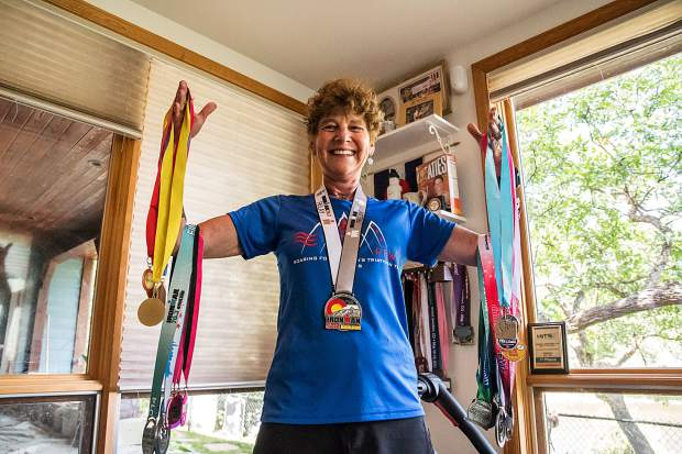 In this July 2018 file photo, Nancy Reinisch holds only a fraction of the medals she has collected over the years of racing and competing in triathlons and other races.