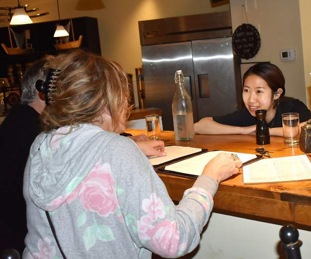 Desy Lin, co-owner of 450 Teppanyaki, assists customers at the counter Monday evening.