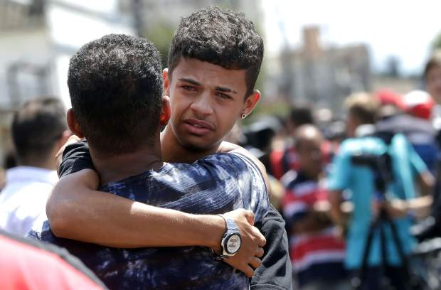A former student is comforted by a friend outside the Raul Brasil State School in Suzano, the greater Sao Paulo area, Brazil, Wednesday, March 13, 2019. The state government of Sao Paulo said two teenagers, armed with guns and wearing hoods, entered the school and began shooting at students. They then killed themselves, according to the statement. (AP Photo/Andre Penner)
