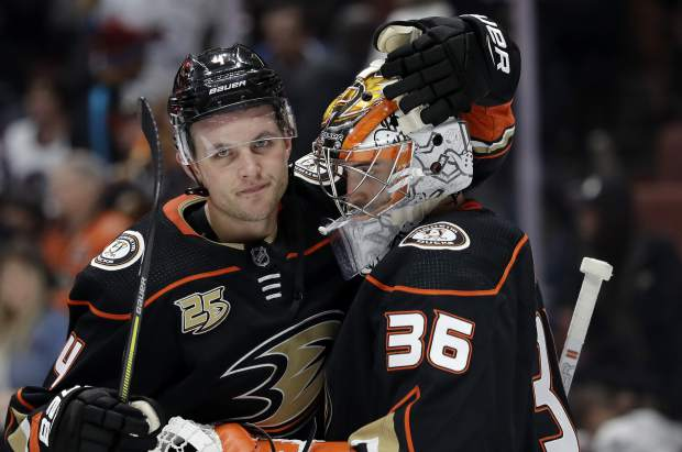 Anaheim Ducks' Cam Fowler, left, hugs teammate John Gibson (36) after a win over the Colorado Avalanche during an NHL hockey game Sunday, March 3, 2019, in Anaheim, Calif. (AP Photo/Marcio Jose Sanchez)