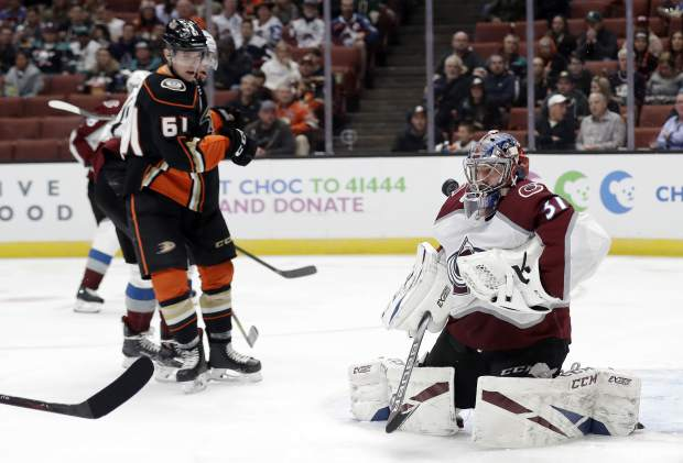 Colorado Avalanche goaltender Philipp Grubauer, right, deflects a shot on goal during the second period of an NHL hockey game against the Anaheim Ducks, Sunday, March 3, 2019, in Anaheim, Calif. (AP Photo/Marcio Jose Sanchez)