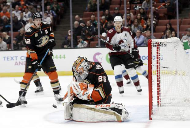 Anaheim Ducks goalie John Gibson, center, stops a shot on goal during the first period of an NHL hockey game against the Colorado Avalanche Sunday, March 3, 2019, in Anaheim, Calif. (AP Photo/Marcio Jose Sanchez)