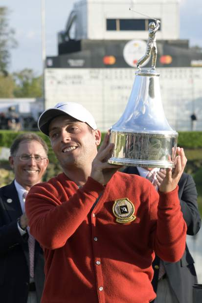 Francesco Molinari, of Italy, lifts the championship trophy after winning the Arnold Palmer Invitational golf tournament Sunday, March 10, 2019, in Orlando, Fla. (AP Photo/Phelan M. Ebenhack)