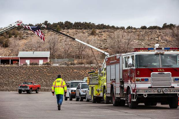 A CDOT worker walks along the fire trucks, assembled in honor of Eric Hill, at Saturday's memorial service held at the Eagle River Center at the Eagle County Faigrounds.