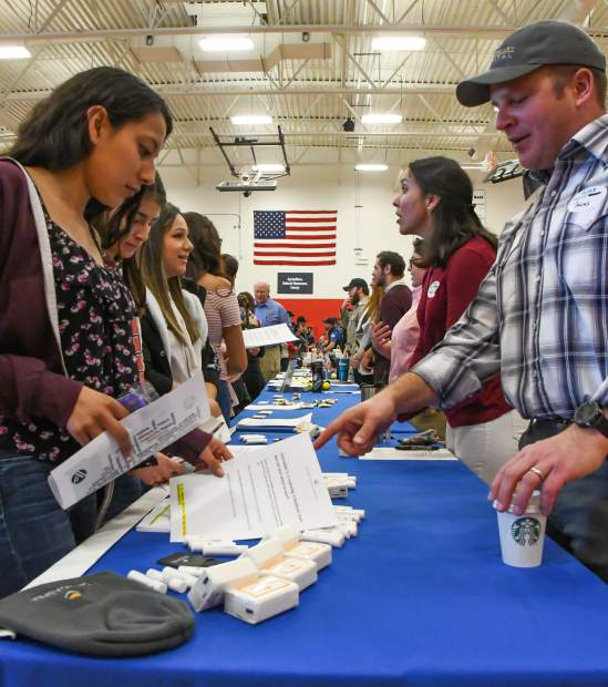 Students approach tables and speak with representatives from 150 businesses at the GlenX Career Expo at Glenwood Springs High School on Tuesday morning.