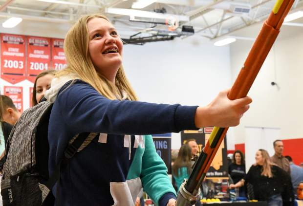 Glenwood Springs High School freshman Sophie McGhee attempts to replace a fuse cutout with a hot stick pole at the Holy Cross Energy table at the GlenX Career Expo.