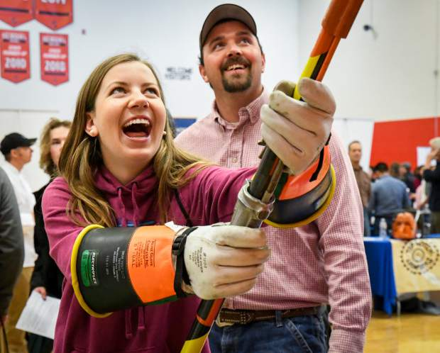 Glenwood Springs High School freshman Emma Barsness attempts to replace a fuse cutout with a hot stick pole at the Holy Cross Energy table at the GlenX Career Expo.
