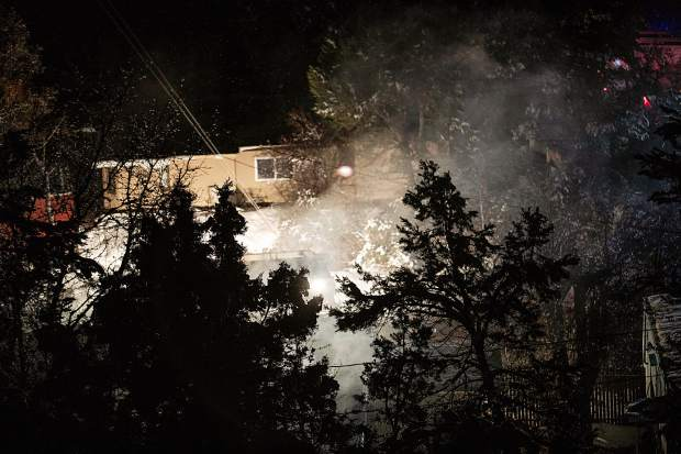 Smoke rolls out of the Garcia's mobile home on Homestead Drive on Saturday night.