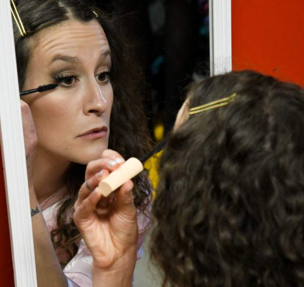 A model does her own make-up backstage prior to the start of the show in Friday evening.