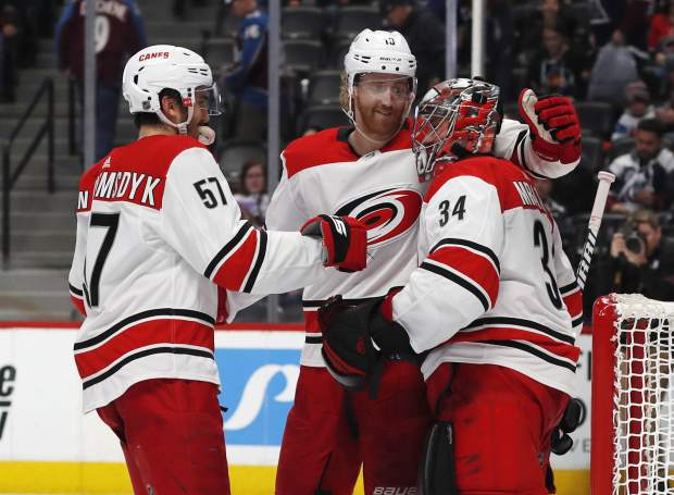 From left, Carolina Hurricanes defensemen Trevor van Riemsdyk, Dougie Hamilton and goaltender Petr Mrazek celebrate as time runs out in the third period of an NHL hockey game against the Colorado Avalanche, Monday, March 11, 2019, in Denver. Carolina won 3-0. (AP Photo/David Zalubowski)