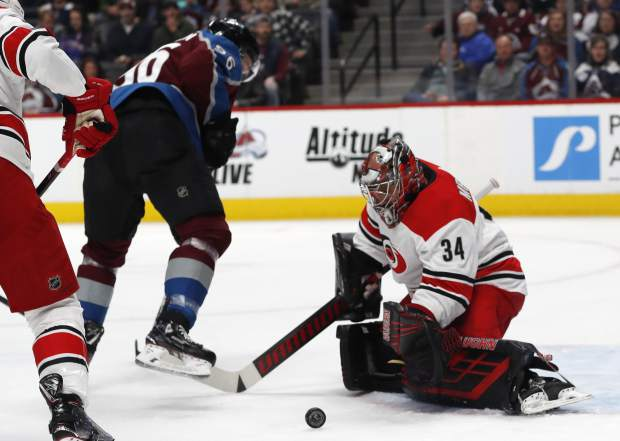 Carolina Hurricanes goaltender Petr Mrazek, right, stops a shot off the stick of Colorado Avalanche right wing Mikko Rantanen in the first period of an NHL hockey game Monday, March 11, 2019, in Denver. (AP Photo/David Zalubowski)