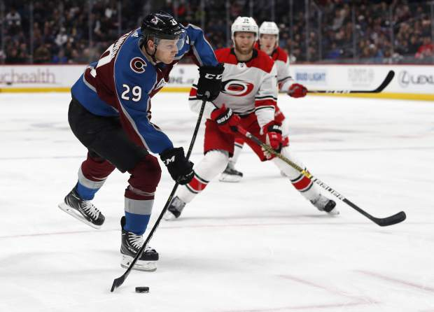 Colorado Avalanche center Nathan MacKinnon, front, shoots the puck as Carolina Hurricanes defenseman Jaccob Slavin covers in the first period of an NHL hockey game Monday, March 11, 2019, in Denver. (AP Photo/David Zalubowski)