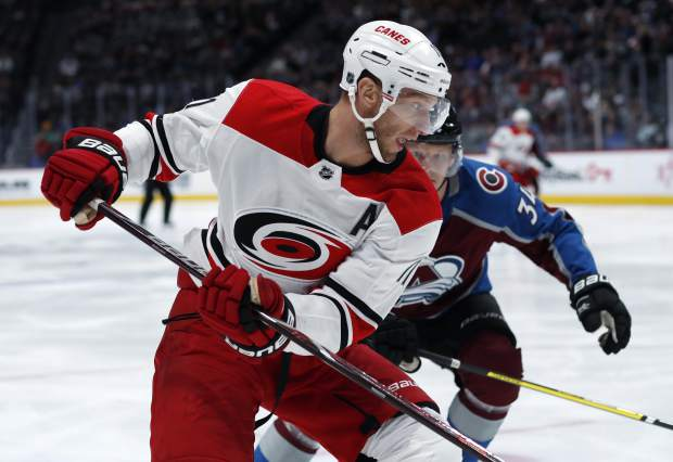 Carolina Hurricanes center Jordan Staal, front, looks to collect the puck as Colorado Avalanche center Carl Soderberg comes in to defend in the first period of an NHL hockey game Monday, March 11, 2019, in Denver. (AP Photo/David Zalubowski)