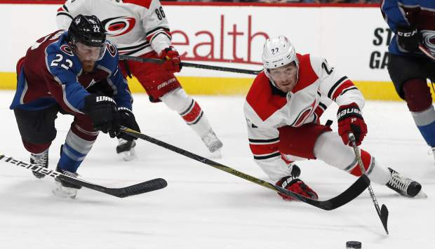 Colorado Avalanche center Colin Wilson, left, reaches out to control the puck with Carolina Hurricanes defenseman Brett Pesce in the first period of an NHL hockey game Monday, March 11, 2019, in Denver. (AP Photo/David Zalubowski)