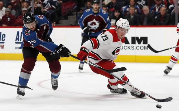 Colorado Avalanche center Nathan MacKinnon, left, fires the puck past Carolina Hurricanes left wing Brock McGinn in the third period of an NHL hockey game, Monday, March 11, 2019, in Denver. Carolina won 3-0. (AP Photo/David Zalubowski)