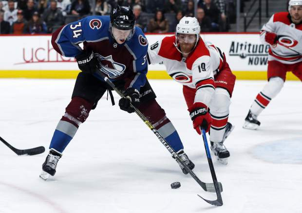 Carolina Hurricanes defenseman Dougie Hamilton, right, knocks the puck away from Colorado Avalanche center Carl Soderberg in the third period of an NHL hockey game, Monday, March 11, 2019, in Denver. Carolina won 3-0. (AP Photo/David Zalubowski)
