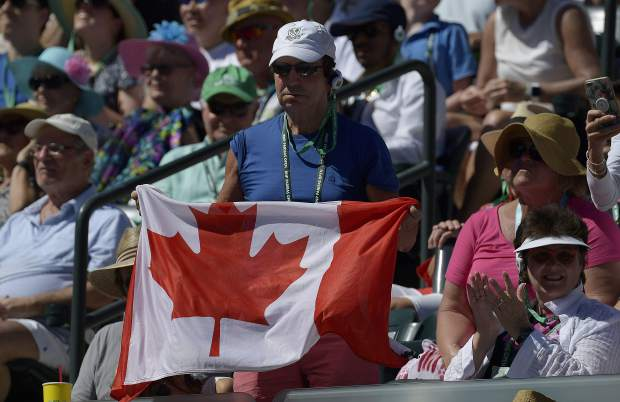 A fan holds up a flag for Bianca Andreescu, of Canada, during the women's final between Andreescu and Angelique Kerber, of Germany, at the BNP Paribas Open tennis tournament Sunday, March 17, 2019, in Indian Wells, Calif. (AP Photo/Mark J. Terrill)