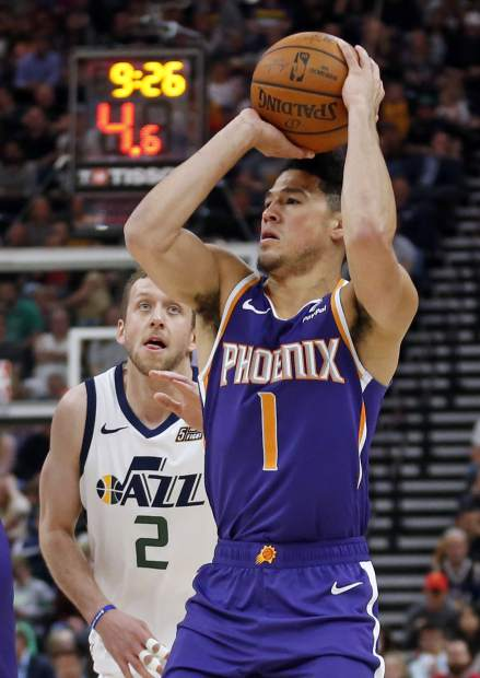 Phoenix Suns guard Devin Booker (1) prepares to shoot as Utah Jazz forward Joe Ingles (2) defends during the first half of an NBA basketball game Monday, March 25, 2019, in Salt Lake City. (AP Photo/Rick Bowmer)
