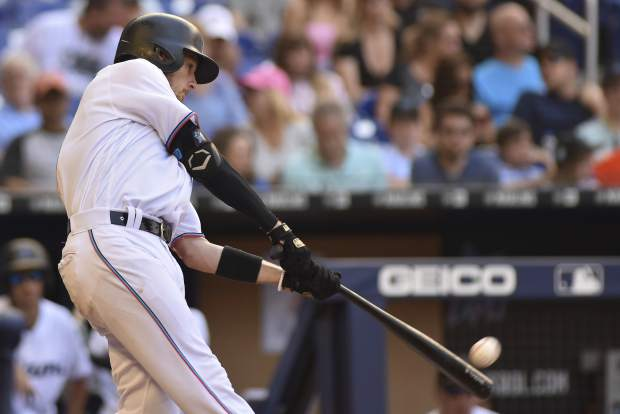 Miami Marlins' JT Riddle hits a solo homer during the seventh inning of a baseball game against the Colorado Rockies, Sunday, March 31, 2019, in Miami. The Marlins won 3-0. (AP Photo/Gaston De Cardenas)