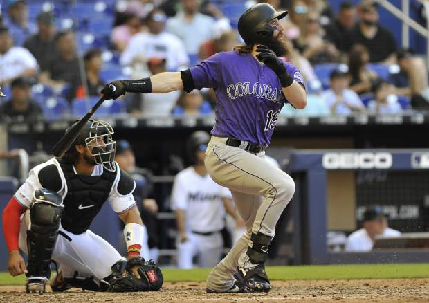 Colorado Rockies' Charlie Blackmon, right, doubles to left field in the ninth inning of a baseball game against the Miami Marlins, Sunday, March 31, 2019, in Miami. (AP Photo/Gaston De Cardenas)