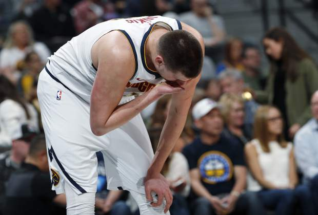 Denver Nuggets center Nikola Jokic holds his nose after getting hit in the face as Washington Wizards forward Bobby Portis drove the lane for a basket in the first half of an NBA basketball game Sunday, March 31, 2019, in Denver. (AP Photo/David Zalubowski)