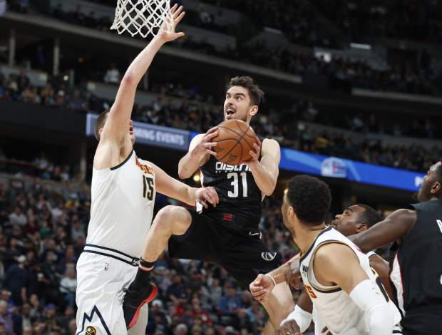 Washington Wizards guard Tomas Satoransky, center, drives the lane for a basket between Denver Nuggets center Nikola Jokic, left, and guard Jamal Murray in the first half of an NBA basketball game Sunday, March 31, 2019, in Denver. (AP Photo/David Zalubowski)