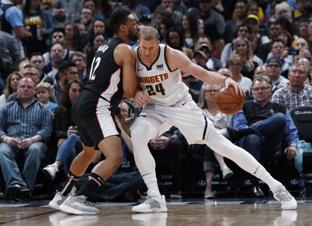 Denver Nuggets forward Mason Plumlee, right, leans into Washington Wizards forward Jabari Parker while working the ball inside for a basket in the first half of an NBA basketball game Sunday, March 31, 2019, in Denver. (AP Photo/David Zalubowski)
