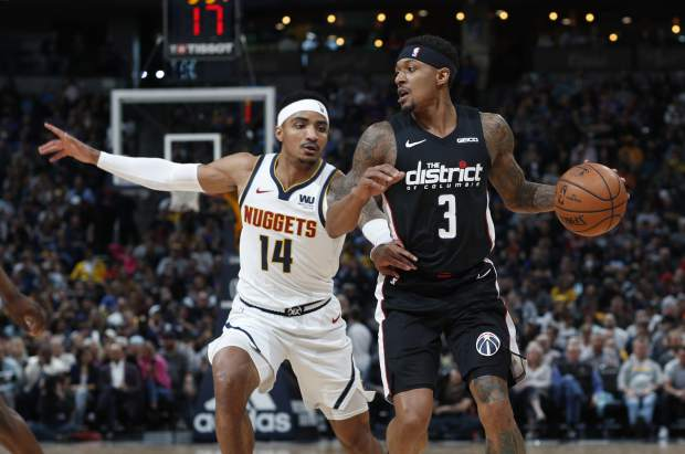 Washington Wizards guard Bradley Beal, right, drives past Denver Nuggets guard Gary Harris in the first half of an NBA basketball game Sunday, March 31, 2019, in Denver. (AP Photo/David Zalubowski)