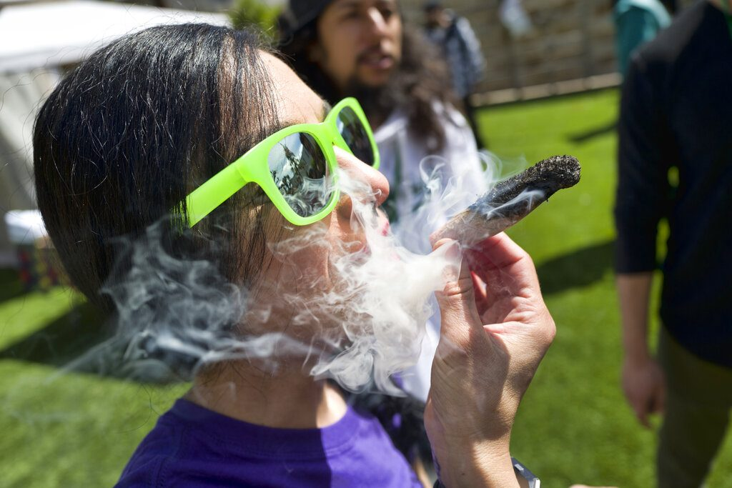 FILE - In this Friday, March 22, 2019 file photo, a participant takes a very smoky puff from a marijuana cigarette during at meet and greet at