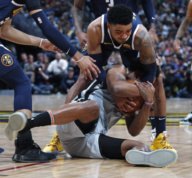 Denver Nuggets guard Gary Harris, top, fights for control of the ball with San Antonio Spurs forward Rudy Gay in the first half of Game 7 of an NBA basketball first-round playoff series Saturday, April 27, 2019, in Denver. (AP Photo/David Zalubowski)