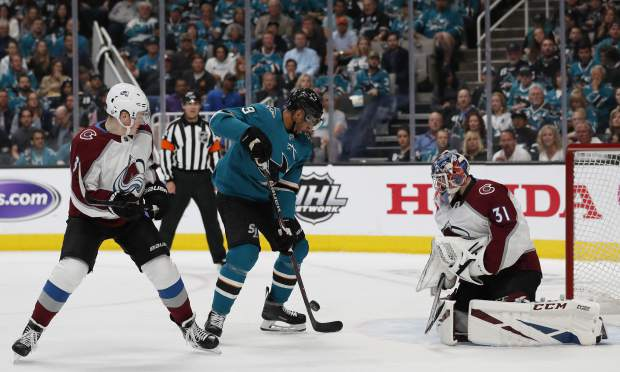 Colorado Avalanche's Cale Maker (8) watches as San Jose Sharks' Evander Kane (9) shoots to score against Colorado Avalanche goaltender Philipp Grubauer (31) in the first period of Game 2 of an NHL hockey second-round playoff series at the SAP Center in San Jose, Calif., on Sunday, April 28, 2019. (AP Photo/Josie Lepe)