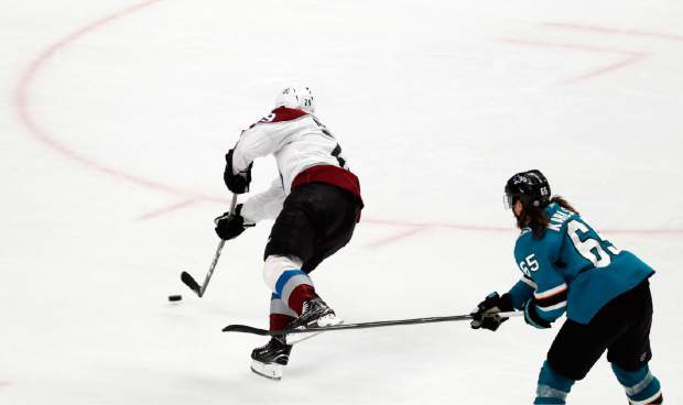 Colorado Avalanche's Nathan MacKinnon (29) shoots to score a goal against San Jose Sharks' Erik Karlsson (65) in the third period of Game 2 of an NHL hockey second-round playoff series at the SAP Center in San Jose, Calif., on Sunday, April 28, 2019. (AP Photo/Josie Lepe)