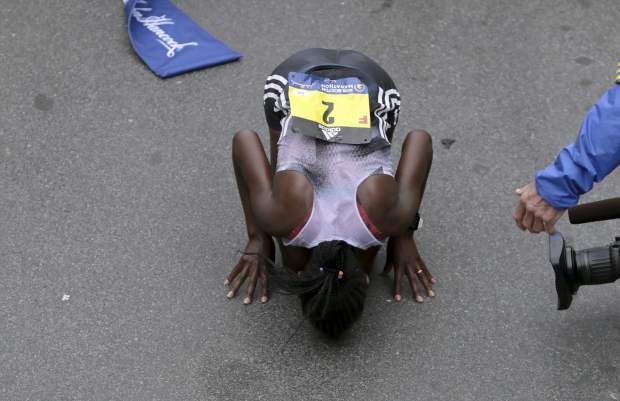 Worknesh Degefa, of Ethiopia, kisses the ground after winning the women's division of the 123rd Boston Marathon on Monday in Boston.