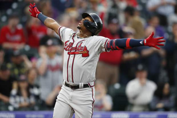Atlanta Braves' Ronald Acuna Jr. celebrates as he crosses home plate after hitting a two-run home run off Colorado Rockies starting pitcher Kyle Freeland in the first inning of a baseball game Monday, April 8, 2019, in Denver. (AP Photo/David Zalubowski)