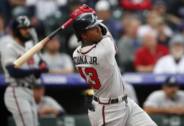 Atlanta Braves' Ronald Acuna Jr. follows the flight of his two-run home run off Colorado Rockies starting pitcher Kyle Freeland in the first inning of a baseball game Monday, April 8, 2019, in Denver. (AP Photo/David Zalubowski)