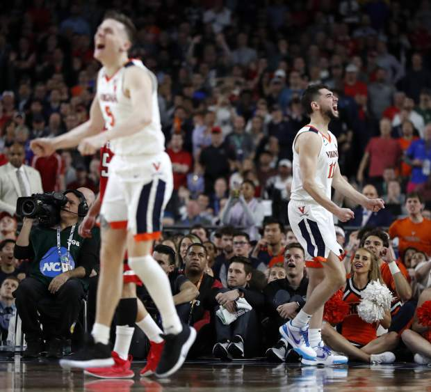 Virginia's Kyle Guy (5) and Ty Jerome (11) react to a play during the overtime in the championship of the Final Four NCAA college basketball tournament against Texas Tech, Monday, April 8, 2019, in Minneapolis. (AP Photo/Jeff Roberson)