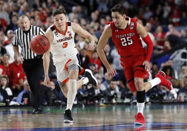 Virginia's Kyle Guy (5) and Texas Tech's Davide Moretti (25) chase a loose ball during the overtime in the championship of the Final Four NCAA college basketball tournament, Monday, April 8, 2019, in Minneapolis. (AP Photo/Jeff Roberson)
