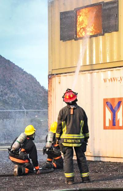 Lead instructor Denny Hostetler watches on as two trainees work to extinguish flames during a structure fire training.