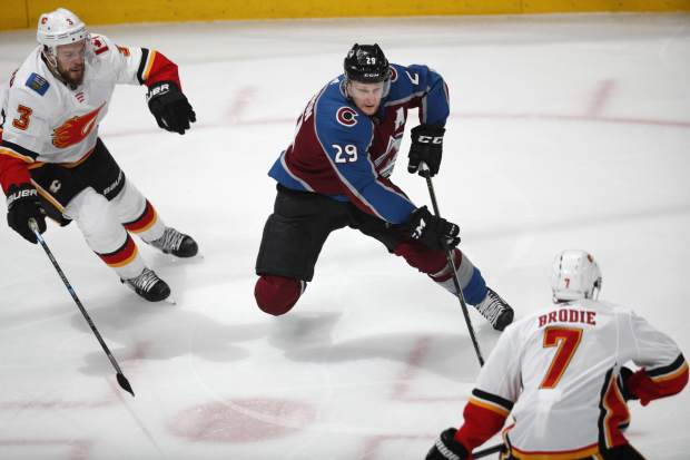 Colorado Avalanche center Nathan MacKinnon, center, drives to the net between Calgary Flames defensemen Oscar Fantenberg, left, and TJ Brodie in the first period of Game 3 of a first-round NHL hockey playoff series Monday, April 15, 2019, in Denver. (AP Photo/David Zalubowski)