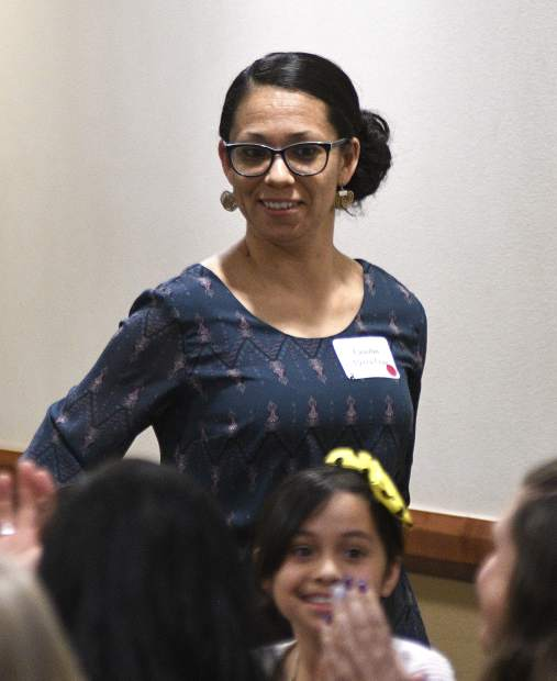 A surprised Claudia Flores Cruz stands up to accept her 2019 Garfield County Humanitarian Service Award Monday at Grand River Health in Rifle.