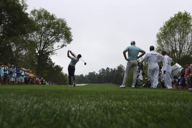 Dustin Johnson looks on as Rory McIlroy tees off on the fifth hole during a practice round for the Masters golf tournament in Augusta, Ga., Monday, April 8, 2019. (Curtis Compton/Atlanta Journal-Constitution via AP)