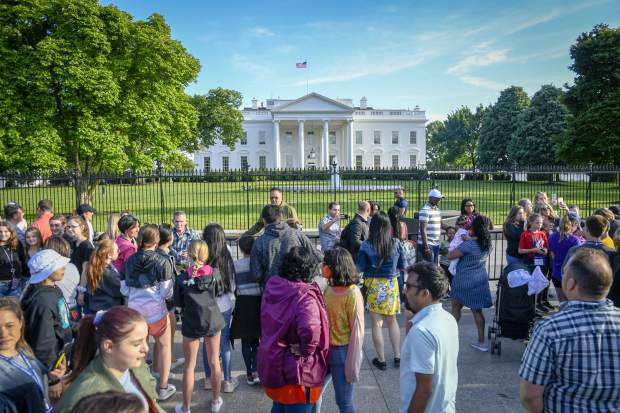 People crowd in front of the White House for a picture of the most famous residence in the United States.