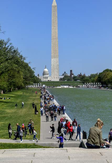 Crowds gather along the Reflecting Pool in the National Mall in the nations capital. The mall holds many of the iconic buildings in Washington D.C., including the Washington, World War II, Lincoln Memorials and more.