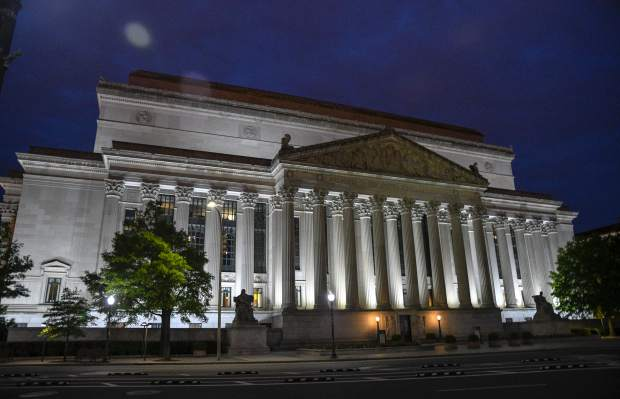 The National Archives Building glows as dusk sets on Pennsylvania Avenue near the United States Navy Memorial. Built in the early 1930's the archives is the home to the original copies of the Declaration of Independence, Bill of Rights and the Constitution.