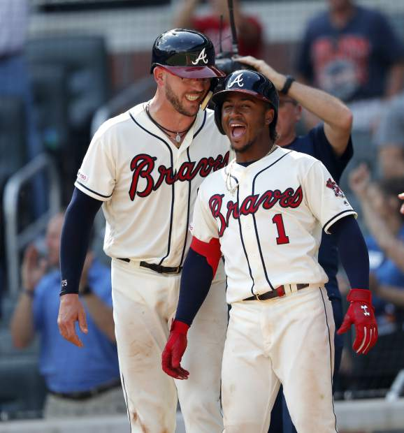 Atlanta Braves' Ozzie Albies (1) and Tyler Flowers wait for teammate Josh Donaldson at home plate after scoring on a there-run home run by Donaldson in the eighth inning of a baseball game against the Colorado Rockies, Sunday, April 28, 2019, in Atlanta. (AP Photo/John Bazemore)