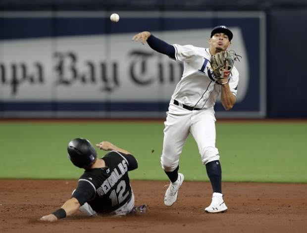 Tampa Bay Rays shortstop Willy Adames forces Colorado Rockies' Mark Reynolds at second base and relays the throw to first in time to turn a double play on Charlie Blackmon during the third inning of a baseball game Monday, April 1, 2019, in St. Petersburg, Fla. (AP Photo/Chris O'Meara)